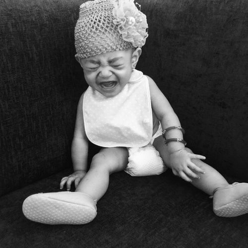 Cute baby girl crying while sitting on sofa at home