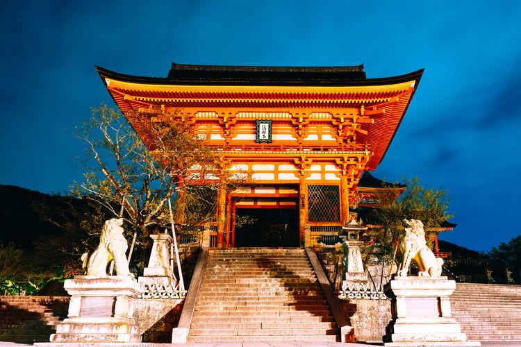 Exterior of illuminated temple building against sky