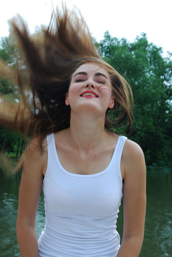 Cheerful young woman tossing hair while standing against lake in park