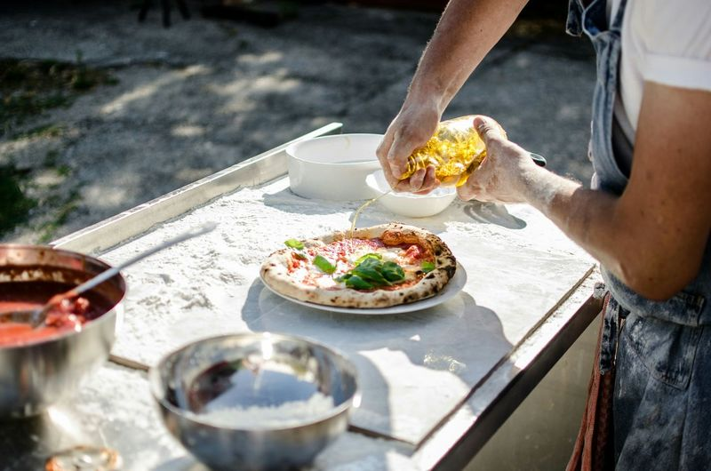 Cropped man pouring oil on pizza on plate in back yard