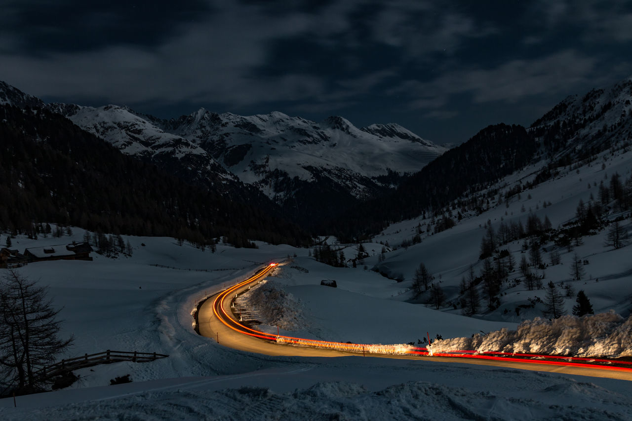 Light trails on road by snow covered field at dusk