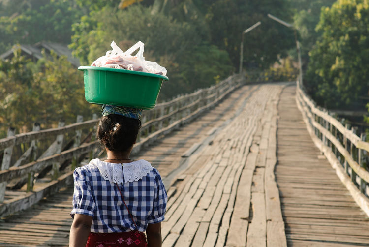 Rear view of woman carrying bucket on footbridge