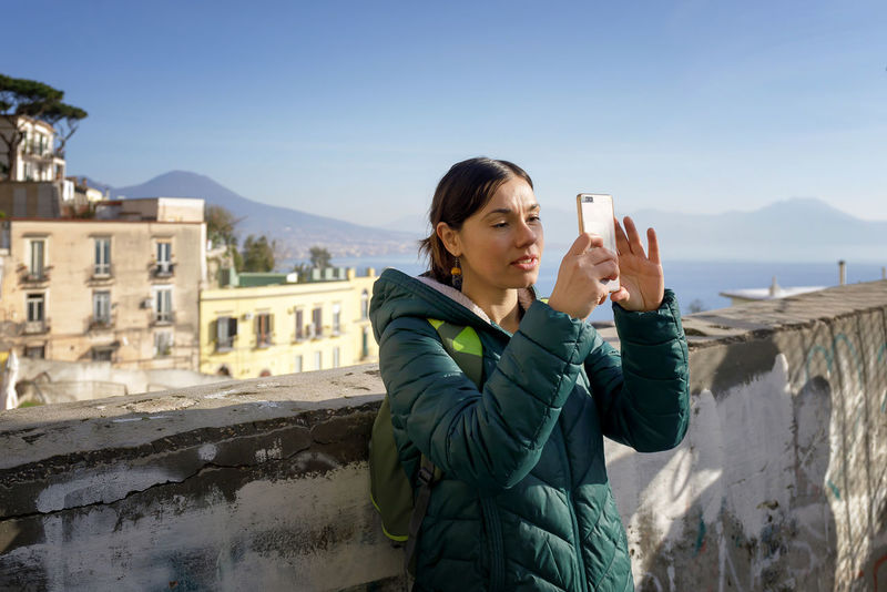 Girl takes a selfie from a vantage point in the city. In the background the classic and unmistakable profile of the Vesuvius volcano, a characteristic element of the city of Naples. One Person Real People Winter Lifestyles Young Adult Architecture Standing Holding Leisure Activity Photography Themes Nature Sky Technology Warm Clothing Wireless Technology Young Women Day Built Structure Women Outdoors Skyline Tourist Panorama View