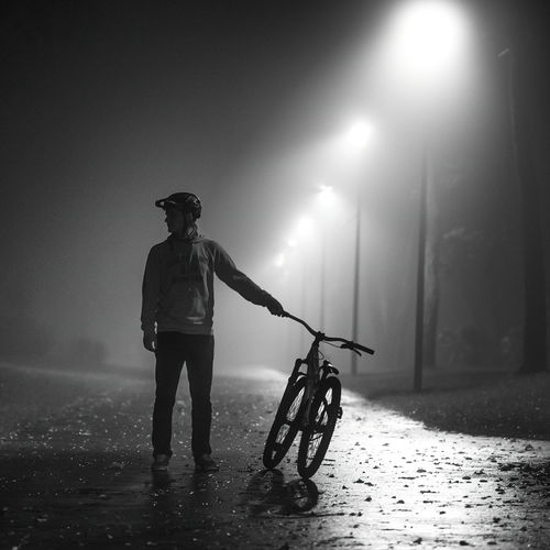 Silhouette man with bicycle standing on street at night