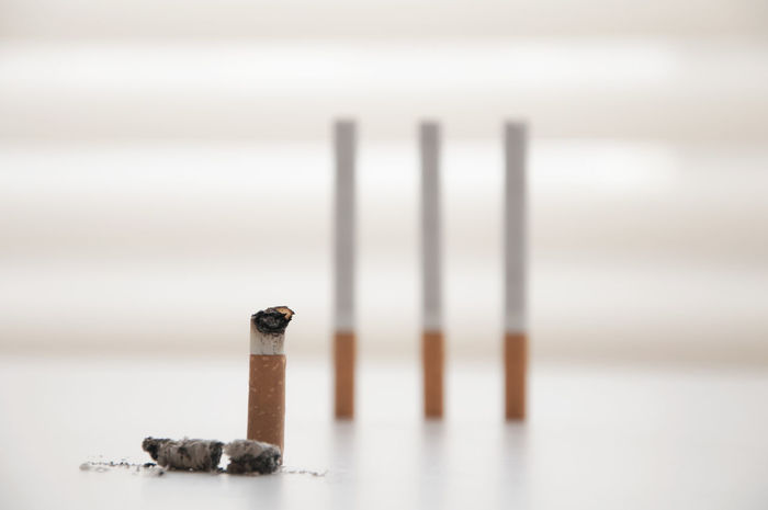 smoked down cigarette in front of a group of standing cigarettes Addiction Ashes Cigarettes Close-up Day Group Group Of Objects Help Indoors  Psycho Shutter Smoked Smoked Down Smoked Out Social Issues Therapy White Background