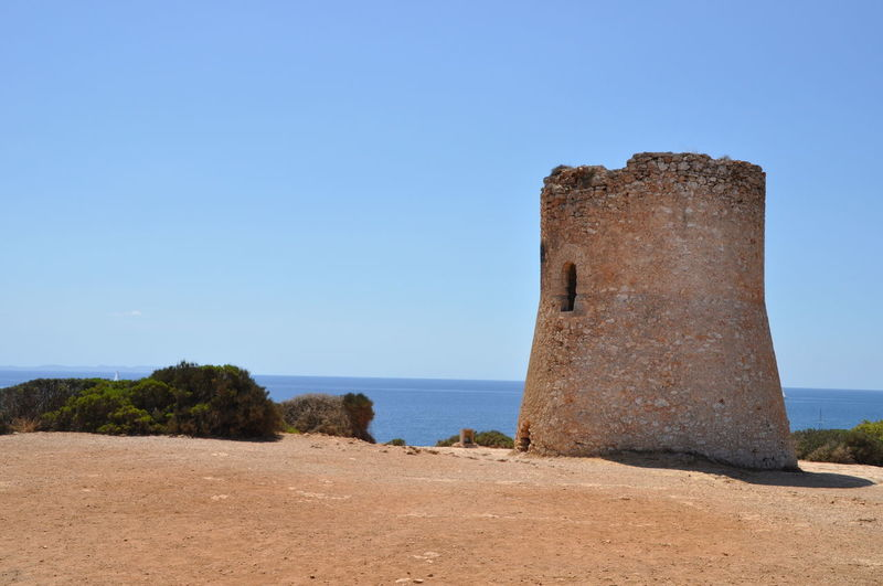 View of ruins at sea against clear blue sky