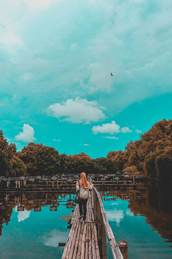 Low angle view of woman standing on riverbank against sky
