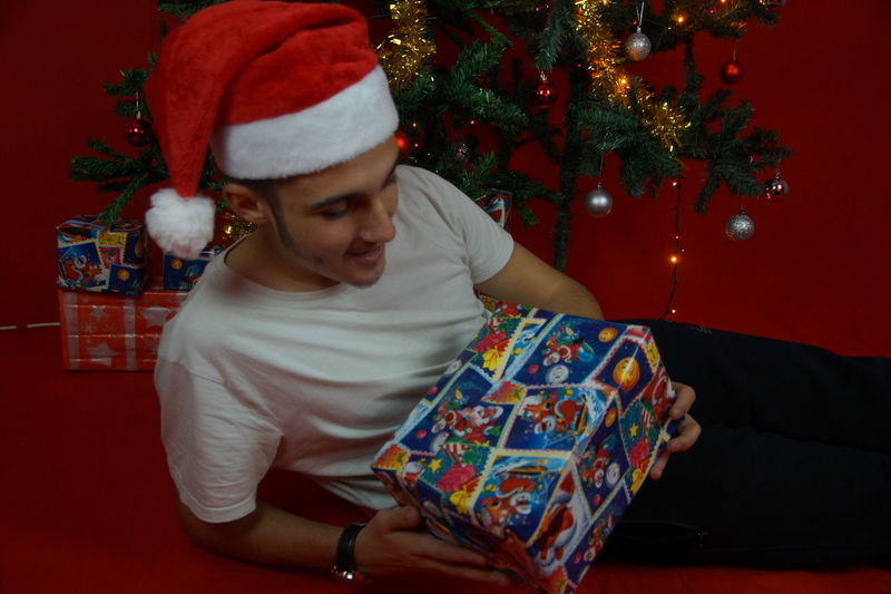 Young man holding christmas present while lying on floor