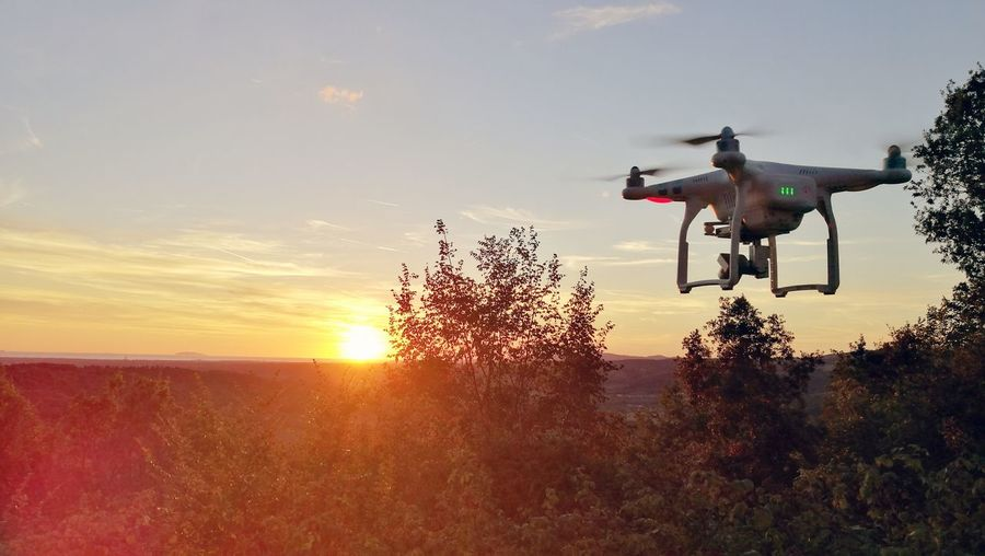 Drone flying over field against sky during sunset