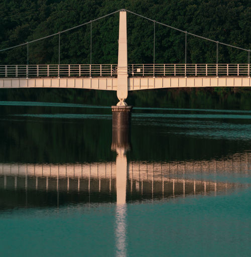 Reflection of bridge over to water pump station at lake in tokyo against blue sky.