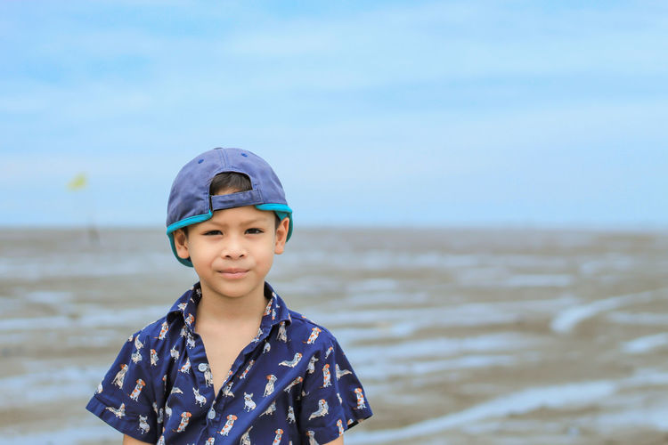 Portrait Of Boy Standing At Beach