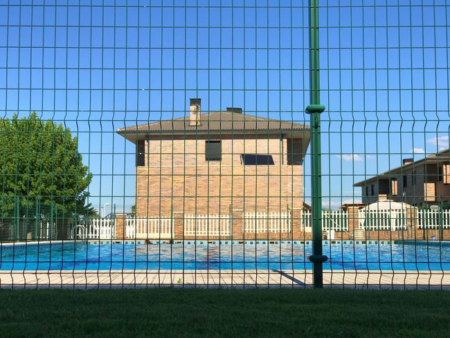 Architecture Built Structure Building Exterior Soccer Field Swimming Swimming Pool Pool Private Security Fence Metallic Fence Safety Summer Enjoying Life Leisure Activity Leisure Swimmingpool Urban Lifestyle Cityscape House Enjoyment City Life Summertime Water Sport