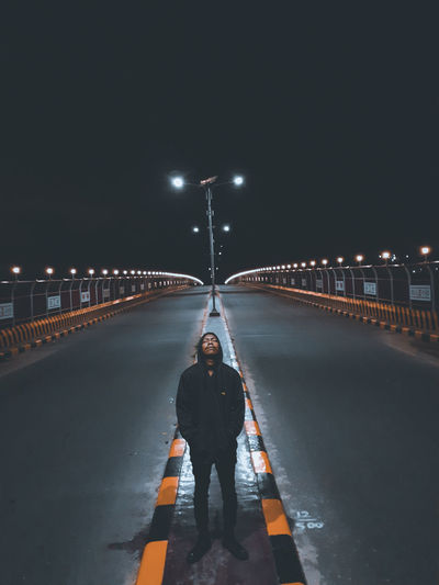 Full length of man standing on illuminated road against sky at night
