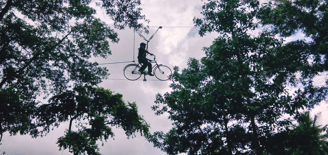 Low angle view of person riding bicycle against sky