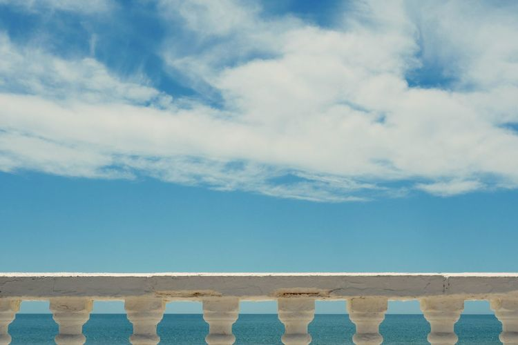 Scenic view of railing by sea against sky