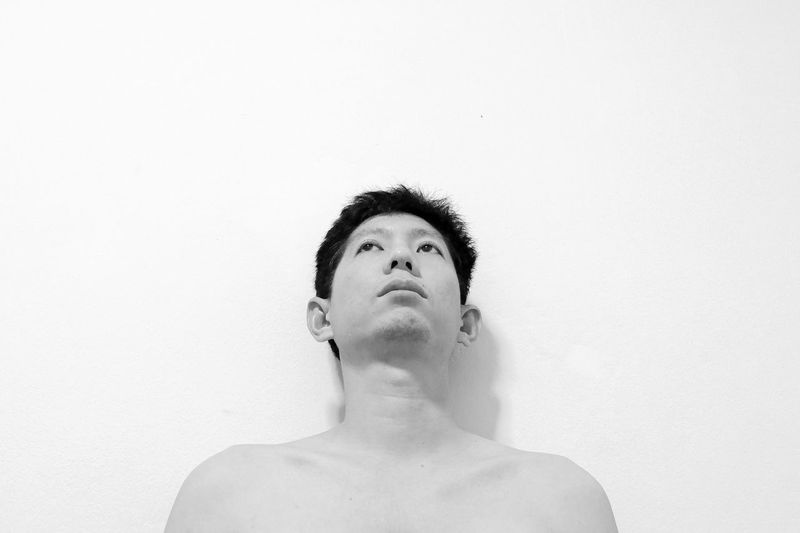 Thoughtful shirtless man against white background
