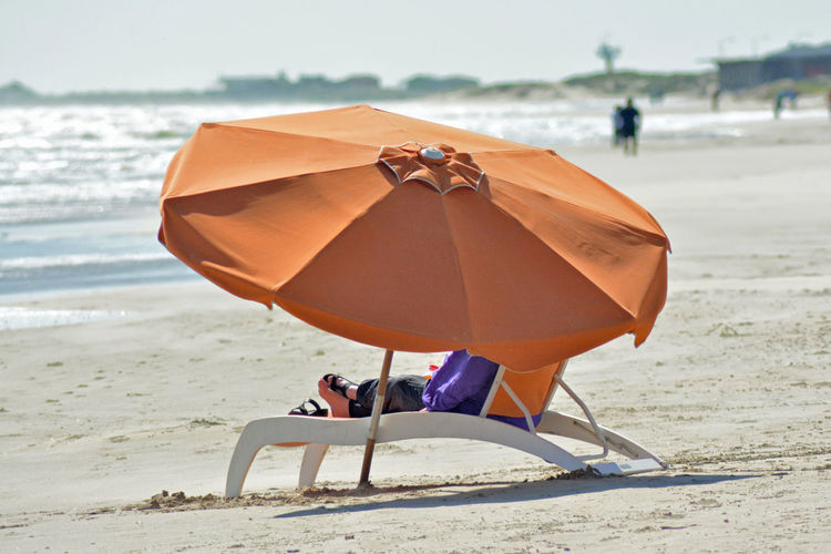 Low section of woman sitting on lounge chair by parasol at beach