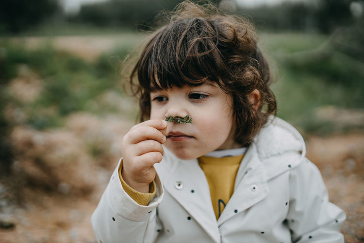Close-up of girl smelling plant outdoors