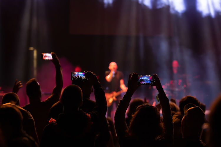 Group of people photographing at music concert