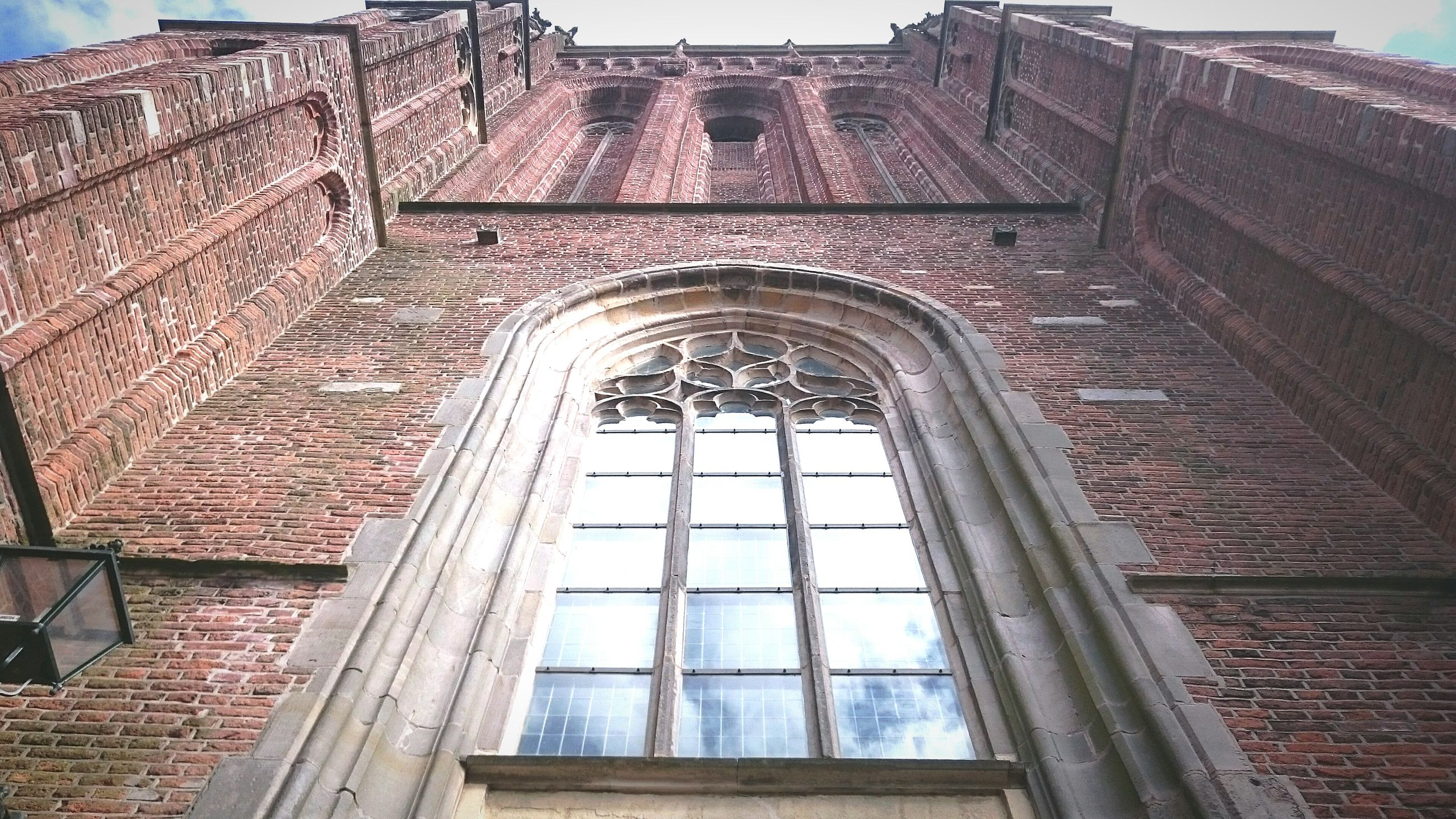 architecture, built structure, building exterior, low angle view, window, arch, brick wall, history, old, building, sky, day, no people, facade, outdoors, architectural feature, stone wall, city, glass - material, tower