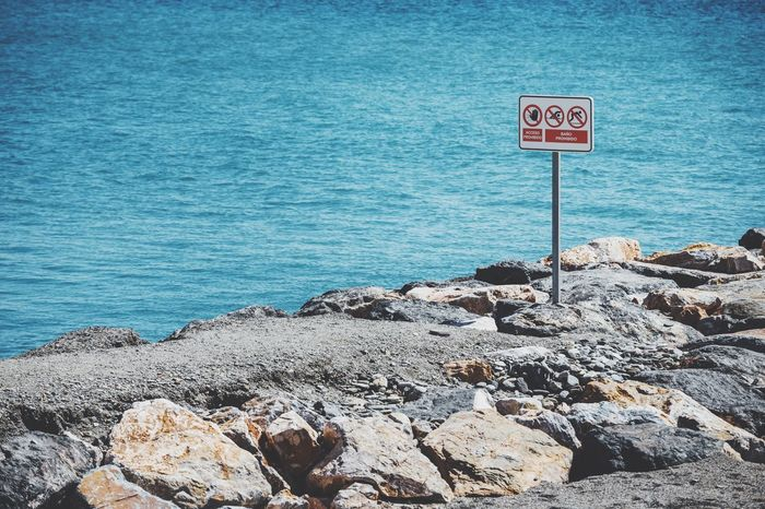 Blue Sea Tranquil Scene Forbidden Places Sign Forbidden Area Rocks Sea Mediterranean  Coast Getting Inspired Nature High Angle View From My Point Of View Outdoors Beach Tranquility Beauty In Nature Rippled Enjoying Life
