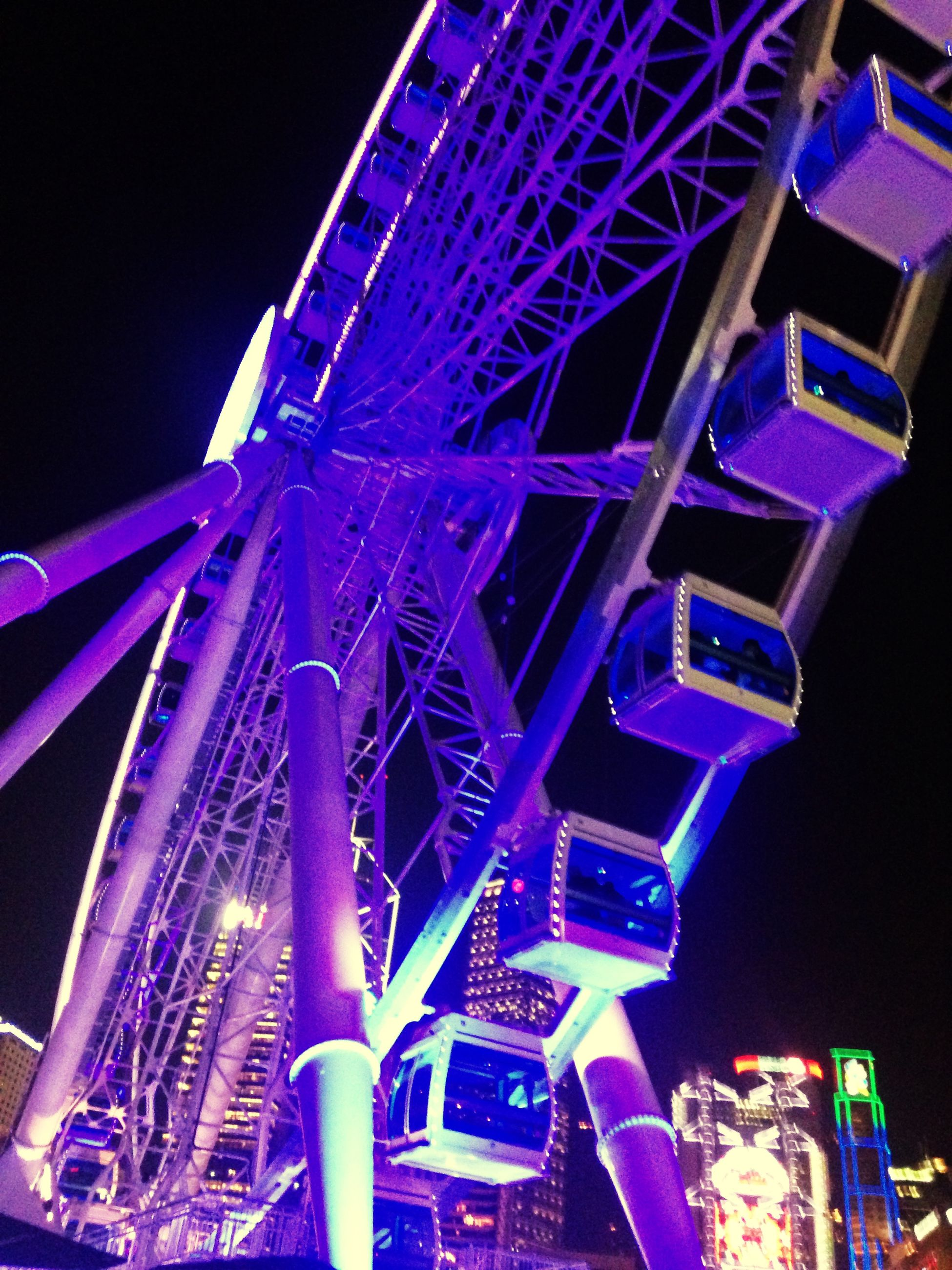 low angle view, architecture, built structure, illuminated, night, building exterior, city, tall - high, tower, modern, arts culture and entertainment, blue, travel destinations, capital cities, famous place, skyscraper, sky, amusement park, lighting equipment, outdoors