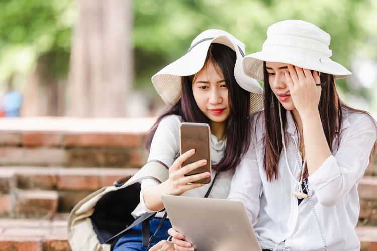 Friends looking away while using mobile phone