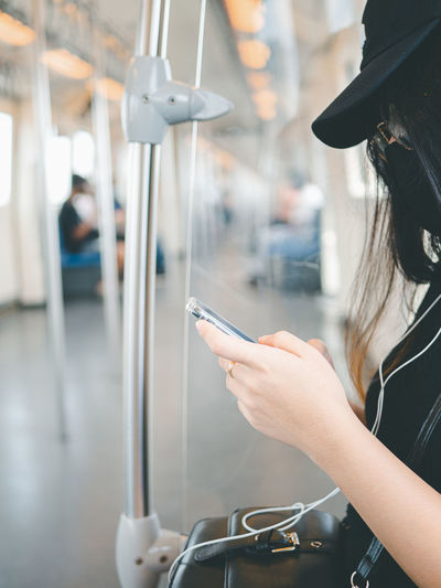 Close-up woman wear protective mask and using smartphone in public transport.