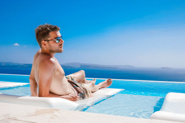 Young Man Relaxing At Infinity Pool Against Sea