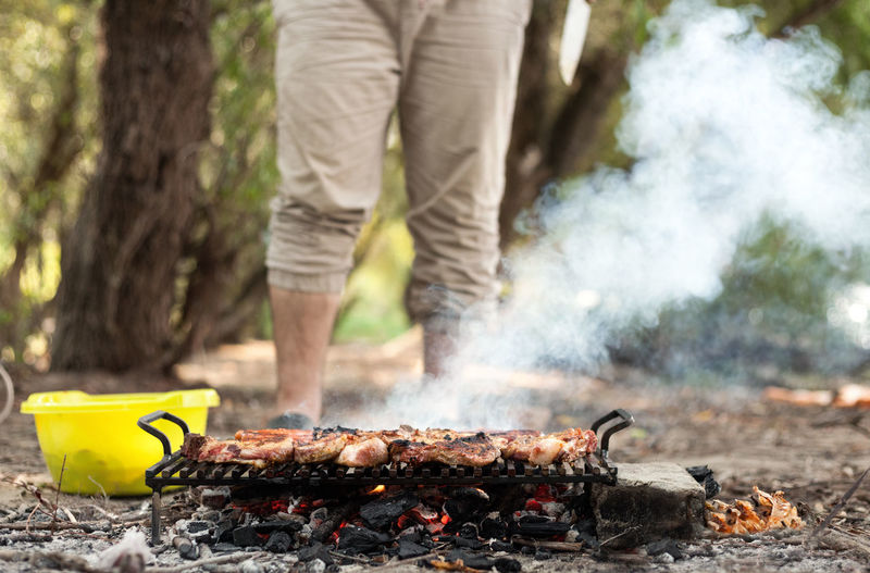 Man preparing meat on barbecue grill