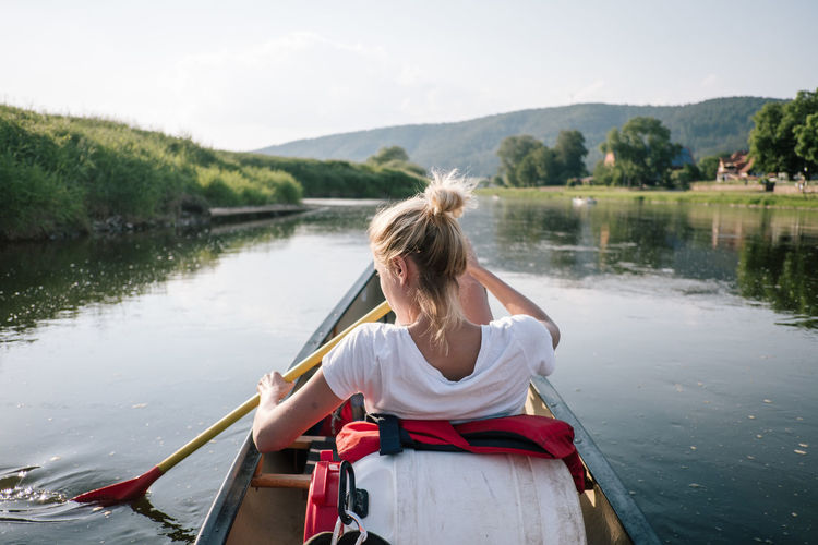 Rear View Of Woman Rowing Boat In Lake