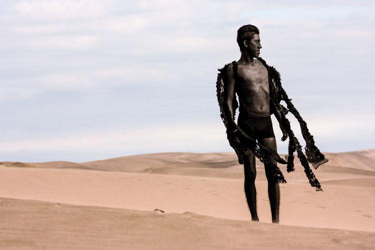 Teenage boy in costume on desert against sky