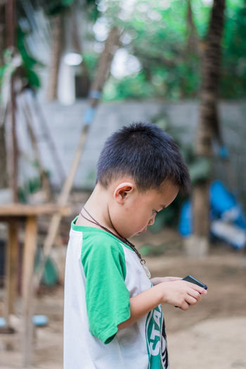 Boy holding mobile phone outdoors