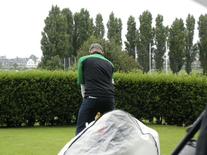 Rear view of golfer taking shot