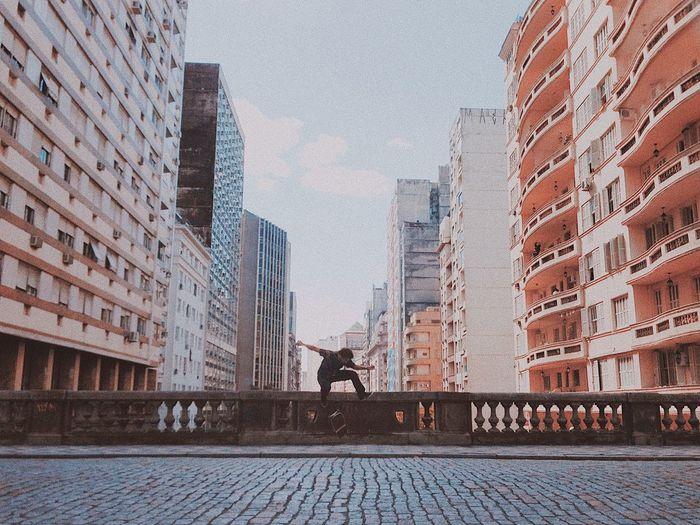Man on street by buildings against sky in city