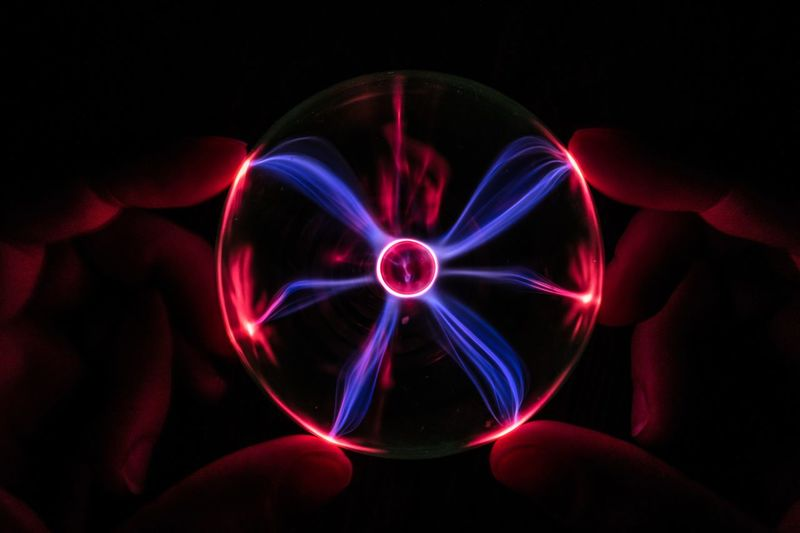 Cropped hands of person holding illuminated crystal ball against black background
