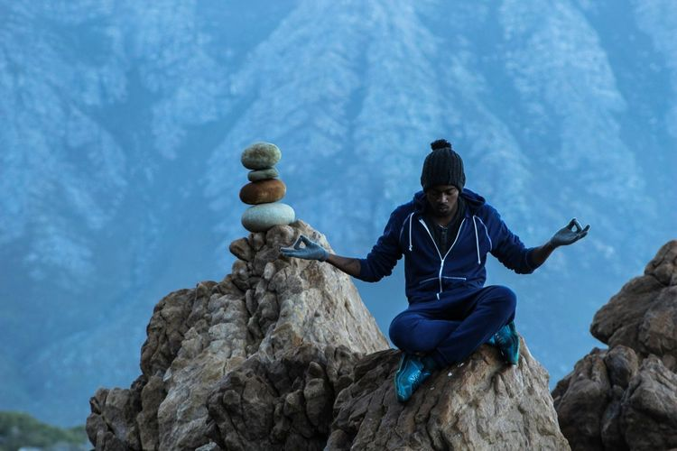 Full length of man meditating while sitting on rock