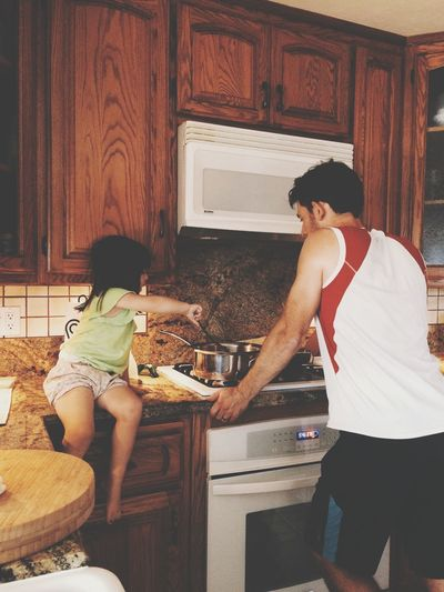 Girl With Father Cooking Food In Kitchen