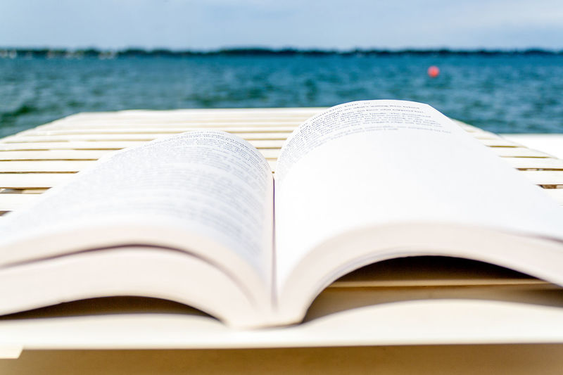 Close-up of open book on table against sea