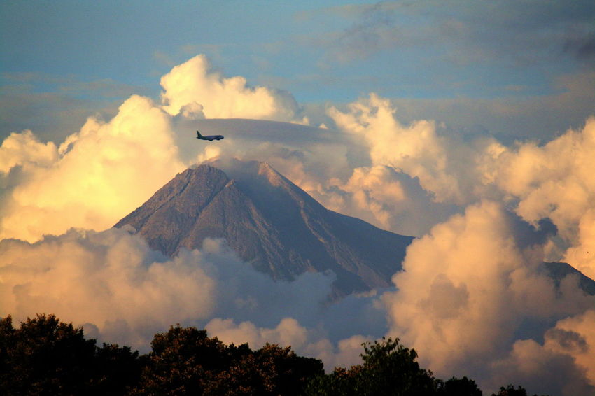 an airplane crossing Mount Merapi Merapi Volcano Yogyakarta Airplane Beauty In Nature Cloud - Sky Day Flying Low Angle View Merapi Mountain , Yogyakarta , Indonesia #mountain #popular #enjoy #indonesia Mountain Nature No People Outdoors Scenics Sky Volcano