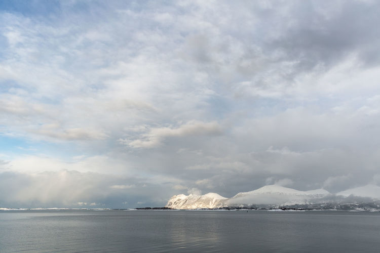 Arctic Atmospheric Mood Cloud Cloudy Dramatic Sky Landscape Mountain Mountain Range Northern Norway Ocean Remote Sea Sea And Sky Seascape Sky Snowcapped Mountains Sunlight Water Waterfront Weather Winter Wintertime Senja