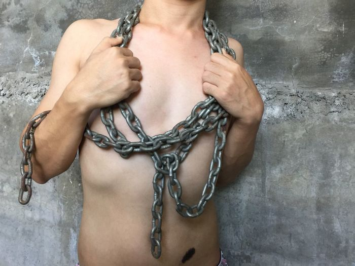 Midsection Of Shirtless Man With Chain Standing Against Wall