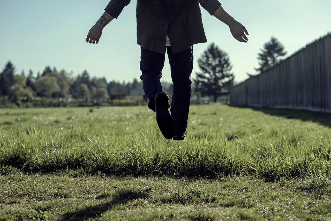 Low section on man levitating over grassy field