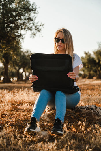 Woman using laptop while sitting at olive orchard