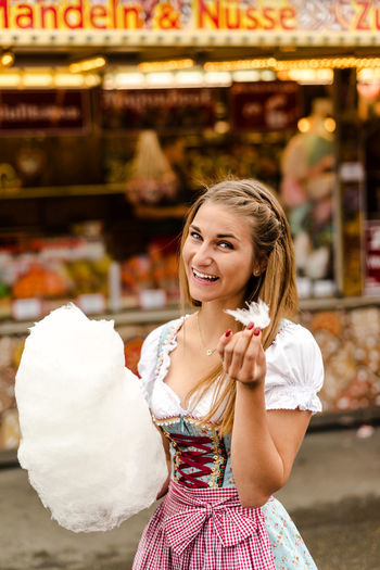 Portrait Of Happy Woman Eating Cotton Candy At Oktoberfest