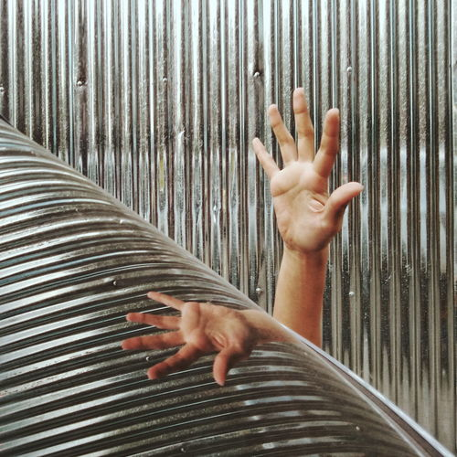 Cropped Hand Trapped Amidst Corrugated Iron