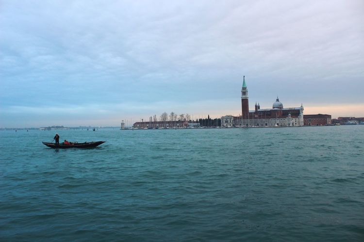 St marks square by grand canal against cloudy sky during sunset