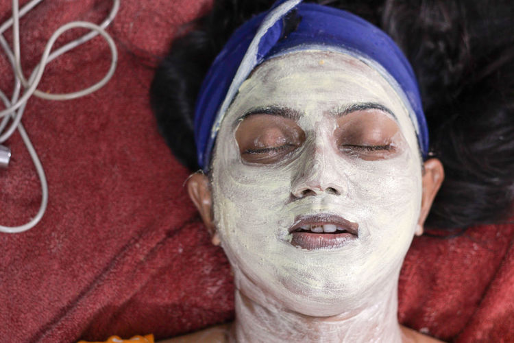 Woman wearing facial mask while lying on bed at home