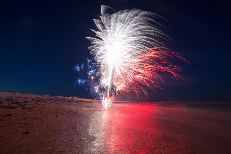 Firework display at beach against sky at dusk