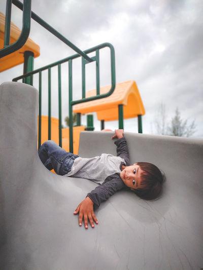 Boy lying on slide at playground